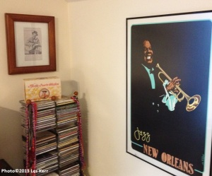 A framed newspaper clipping of Jimmie Rodgers and a Louis Armstrong poster in my office
