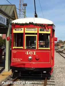 New Orleans streetcar with Christmas garland picks up passengers near Governor Nichols Wharf